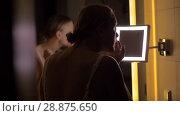 Купить «Woman looking in bathroom mirror after applying facial cream», видеоролик № 28875650, снято 21 августа 2018 г. (c) Данил Руденко / Фотобанк Лори
