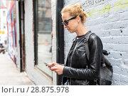 Купить «Woman using smartphone against colorful graffiti wall in New York city, USA.», фото № 28875978, снято 4 апреля 2020 г. (c) Matej Kastelic / Фотобанк Лори