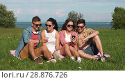 Купить «smiling friends with smartphones sitting on grass», видеоролик № 28876726, снято 19 июля 2018 г. (c) Syda Productions / Фотобанк Лори