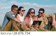 Купить «smiling friends with tablet pc sitting on grass», видеоролик № 28876734, снято 19 июля 2018 г. (c) Syda Productions / Фотобанк Лори