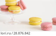 Купить «yellow and pink macarons on glass stand and table», видеоролик № 28876842, снято 13 июля 2018 г. (c) Syda Productions / Фотобанк Лори