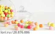 Купить «close up of scattered candy drops and jar on table», видеоролик № 28876886, снято 13 июля 2018 г. (c) Syda Productions / Фотобанк Лори
