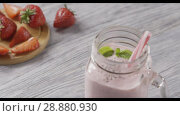 Купить «Panoramic slow motion video of jar with strawberry milk smoothies with chia seeds, a leaf of mint and plastic straws in it. Background of strawberry fruit on a wooden board. Full HD, 240fps,1080p.», видеоролик № 28880930, снято 29 июня 2018 г. (c) Ярослав Данильченко / Фотобанк Лори