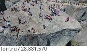Купить «Вид на скалу Проповедника (Preikestolen) и людей, сидящих на краю. Туристическая природная достопримечательность. Норвегия», видеоролик № 28881570, снято 12 июля 2018 г. (c) Кекяляйнен Андрей / Фотобанк Лори