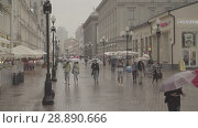 Купить «People walks on Old Arbat street during rainy summer day. Moscow downtown», видеоролик № 28890666, снято 24 июля 2018 г. (c) Ирина Мойсеева / Фотобанк Лори