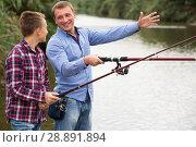 Купить «Man and boy fishing together on freshwater lake», фото № 28891894, снято 17 октября 2018 г. (c) Яков Филимонов / Фотобанк Лори