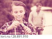 Купить «Teenage boy releasing catch on hook fish on lake», фото № 28891910, снято 21 октября 2018 г. (c) Яков Филимонов / Фотобанк Лори