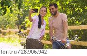 Купить «couple with bicycles taking selfie by smartphone», видеоролик № 28906942, снято 27 июля 2018 г. (c) Syda Productions / Фотобанк Лори
