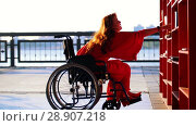 Купить «Young Red-Haired Girl With A Disability In Orange Dress Pulls Up On A Wheelchair To The Bookshelf And Takes The Book», видеоролик № 28907218, снято 26 сентября 2018 г. (c) Константин Шишкин / Фотобанк Лори