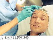Купить «Female specialist is marking zone on face of client», фото № 28907346, снято 21 августа 2018 г. (c) Яков Филимонов / Фотобанк Лори