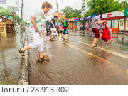 Купить «Russia, Samara, June 2018: A pedestrian crosses the road through deep water after a heavy rainfall.», фото № 28913302, снято 21 июля 2018 г. (c) Акиньшин Владимир / Фотобанк Лори