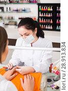 Купить «young manicurist filing and shaping nails in beauty salon», фото № 28913834, снято 28 апреля 2017 г. (c) Яков Филимонов / Фотобанк Лори