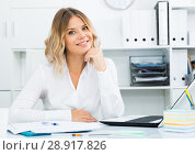 Купить «Smiling girl in white shirt sitting at office desk in well-lit office», фото № 28917826, снято 17 октября 2017 г. (c) Яков Филимонов / Фотобанк Лори