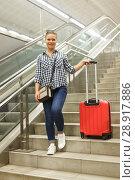 Купить «Girl coming down stairs in subway with suitcase», фото № 28917886, снято 27 апреля 2018 г. (c) Яков Филимонов / Фотобанк Лори