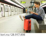 Купить «Smiling girl sitting on bench at metro station», фото № 28917898, снято 27 апреля 2018 г. (c) Яков Филимонов / Фотобанк Лори