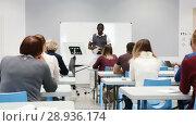 Купить «Smiling African American teacher giving presentation for students in lecture hall», видеоролик № 28936174, снято 23 мая 2018 г. (c) Яков Филимонов / Фотобанк Лори