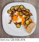 Купить «Plate with scrambled eggs with lard and zucchini at table on table», фото № 28936474, снято 17 августа 2018 г. (c) Яков Филимонов / Фотобанк Лори