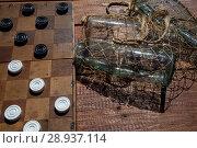 Купить «Настольная игра шашки и пустые бутылки в авоське лежат на деревянном столе», фото № 28937114, снято 11 августа 2018 г. (c) Николай Винокуров / Фотобанк Лори