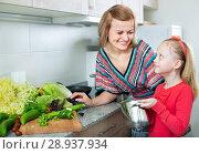 Купить «Young woman and little girl cooking fresh vegetables», фото № 28937934, снято 14 августа 2018 г. (c) Яков Филимонов / Фотобанк Лори