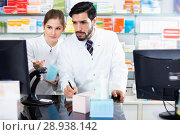 Купить «Two pharmacists are attentively stocktaking medicines with computer and note on paper», фото № 28938142, снято 28 февраля 2018 г. (c) Яков Филимонов / Фотобанк Лори