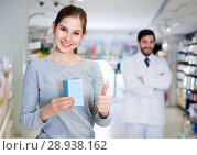 Smiling female client is satisfied of recommended medicine in apothecary. Стоковое фото, фотограф Яков Филимонов / Фотобанк Лори