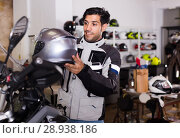 Купить «Man in moto jacket is choosing new helmet for motorbike in the store.», фото № 28938186, снято 1 сентября 2017 г. (c) Яков Филимонов / Фотобанк Лори