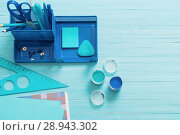 Купить «Collection of blue school supplies on blue wooden background», фото № 28943302, снято 25 декабря 2017 г. (c) Майя Крученкова / Фотобанк Лори