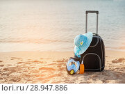 Купить «Suitcase and hat, sunscreen with a mask. The tropical sea, beach in the background. The concept of summer recreation travel and cruise traffic», фото № 28947886, снято 19 апреля 2018 г. (c) Happy Letters / Фотобанк Лори