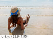 Купить «Summer lifestyle portrait of pretty young suntanned woman in a hat. Enjoying life and sitting on the beach, time to travel. Looking at the sea», фото № 28947954, снято 4 августа 2018 г. (c) Happy Letters / Фотобанк Лори
