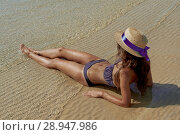 Купить «Summer lifestyle portrait of pretty young suntanned woman in a hat. Enjoying life and sitting on the beach, time to travel. Looking at the sea», фото № 28947986, снято 4 августа 2018 г. (c) Happy Letters / Фотобанк Лори