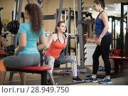 Купить «Pretty girl using barbell in gym. Trainer keep watch over her», фото № 28949750, снято 14 августа 2018 г. (c) Оксана Кузьмина / Фотобанк Лори