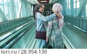 Купить «Two muslim girl was found on the escalator, embraced», видеоролик № 28954130, снято 20 марта 2019 г. (c) Константин Шишкин / Фотобанк Лори