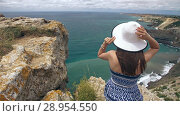Купить «Woman sitting on the rock and watching seascape», видеоролик № 28954550, снято 9 августа 2018 г. (c) Илья Шаматура / Фотобанк Лори