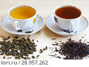 Купить «Two cups of tea, one with green and the second with black hot drink and a dry leaves to brew tea from Oriental green and fermented black leaf tea», фото № 28957262, снято 4 июля 2018 г. (c) Виктория Катьянова / Фотобанк Лори