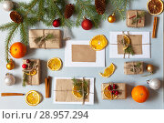 Купить «Merry Christmas. New Year messages and hand-made gifts decorated with dry fragrant mandarin slices on on a light table. Top view. Copy space. Xmas still life», фото № 28957294, снято 25 июля 2018 г. (c) Виктория Катьянова / Фотобанк Лори