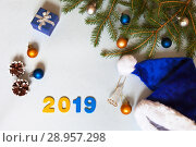 Купить «Branches of a Christmas tree with  with blue and yellow balls and Santa's hat on a light background. New Year's greetings with figures of 2019 and space for text in the center», фото № 28957298, снято 25 июля 2018 г. (c) Виктория Катьянова / Фотобанк Лори