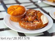 Купить «Muffin and pretzel on a saucer», фото № 28957578, снято 31 июля 2018 г. (c) Юлия Кузнецова / Фотобанк Лори