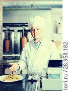 Купить «Chef wearing uniform holding plate with made kebab», фото № 28958182, снято 15 октября 2018 г. (c) Яков Филимонов / Фотобанк Лори