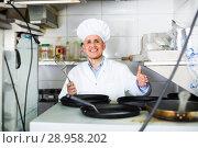 Купить «mature chef with frying pans in kitchen», фото № 28958202, снято 15 октября 2018 г. (c) Яков Филимонов / Фотобанк Лори