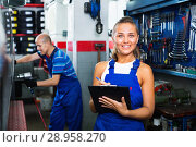 Купить «Portrait of mechanic girl in coveralls having cardboard with documents in hands», фото № 28958270, снято 20 мая 2019 г. (c) Яков Филимонов / Фотобанк Лори