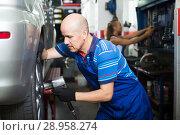 Купить «Happy man technician assembling new tires to car», фото № 28958274, снято 19 сентября 2019 г. (c) Яков Филимонов / Фотобанк Лори