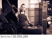 Купить «Young woman technician standing with wheel», фото № 28958286, снято 19 сентября 2019 г. (c) Яков Филимонов / Фотобанк Лори