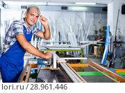 Купить «Confident workman ready to working on circular saw», фото № 28961446, снято 19 июля 2017 г. (c) Яков Филимонов / Фотобанк Лори