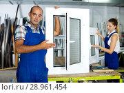 Купить «Workman in blue overalls demonstrating pvc window», фото № 28961454, снято 19 июля 2017 г. (c) Яков Филимонов / Фотобанк Лори