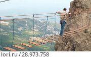 Купить «Man walking by suspension bridge», видеоролик № 28973758, снято 9 августа 2018 г. (c) Илья Шаматура / Фотобанк Лори
