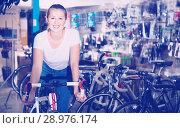 Купить «Portrait of woman who is standing with new bicycle indoors.», фото № 28976174, снято 13 сентября 2017 г. (c) Яков Филимонов / Фотобанк Лори