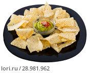 Купить «Corn chips nachos with homemade guacamole sauce on black plate», фото № 28981962, снято 21 ноября 2018 г. (c) Яков Филимонов / Фотобанк Лори