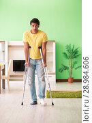 Купить «The young man recovering after accident at home with crutches», фото № 28984606, снято 30 мая 2018 г. (c) Elnur / Фотобанк Лори