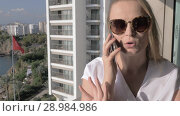 Купить «Emotional woman having mobile phone talk on the balcony with sea view», видеоролик № 28984986, снято 18 ноября 2018 г. (c) Данил Руденко / Фотобанк Лори