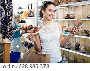Купить «Young woman choosing a pair of shoes», фото № 28985378, снято 21 сентября 2018 г. (c) Яков Филимонов / Фотобанк Лори